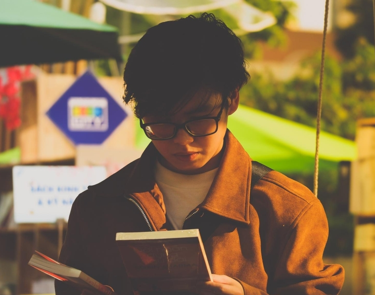 Boy reading book. Photo by Bùi Nam Phong from Pexels.